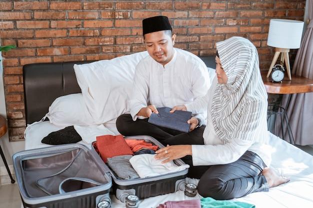 イスラム教徒のカップルがスーツケースに服を準備します。 Premium写真