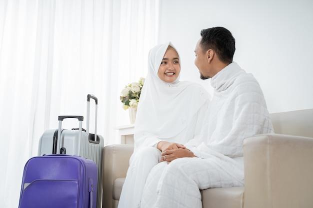 イスラム教徒のカップルは、ウムラの前に白い伝統的な服を着て座っています。 Premium写真