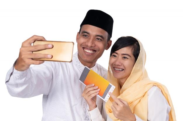 電話でselfieとイスラム教徒のカップル Premium写真