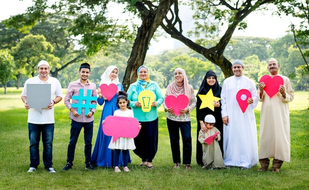 Muslim family holding up various social media icons Premium Photo