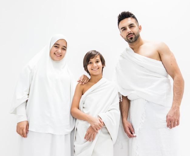Muslim family posing as ready for hajj visiting kaaba in mecca Premium Photo