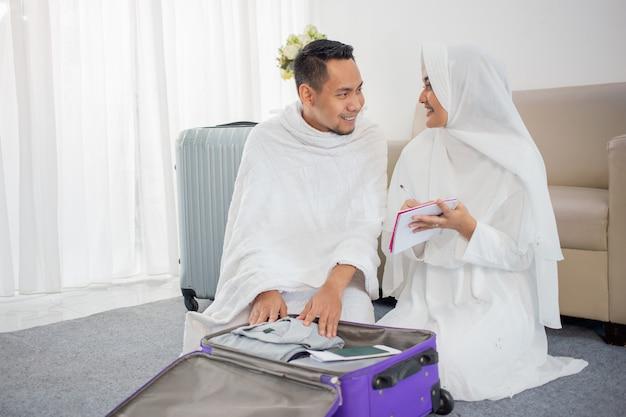 メッカ巡礼前に荷物を準備するイスラム教徒の家族 Premium写真