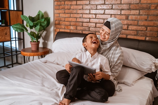 Muslim family using tablet on the bed Premium Photo