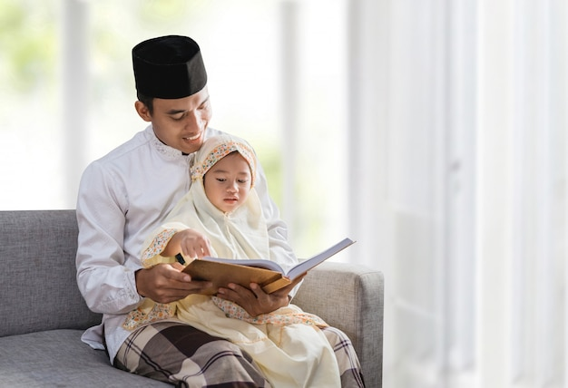 Muslim father read quran with his daughter Premium Photo
