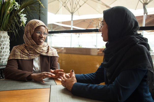Muslim female colleagues chatting during lunch break Free Photo