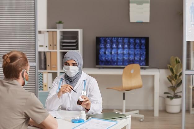 彼らが病院に座っている間に男性患者に薬を処方する保護マスクのイスラム教徒の女性医師 Premium写真