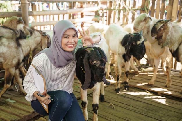 Мусульманка-фермер проверяет свою козу в клетке Premium Фотографии