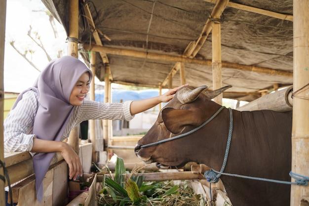 Мусульманская женщина-фермер кормит животных на традиционной ферме Premium Фотографии