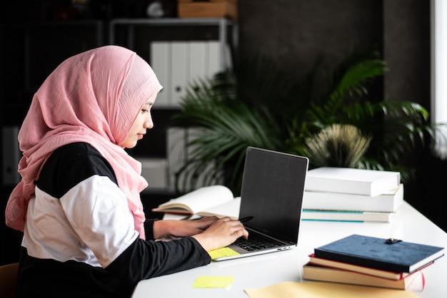 Muslim girl doing work at home Premium Photo