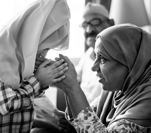 Muslim girl paying respect to mother Free Photo