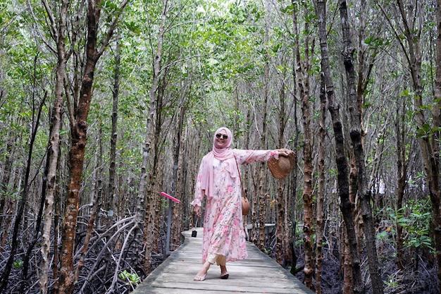 カメラに笑顔のイスラム教徒の少女は、熱帯の海で休暇をお楽しみください。太陽の麦わら帽子とマングローブの森の緑の植物の背景を持つ木製の橋の上に立っている白いドレスを着ているティーンエイジャーの女の子。 Premium写真