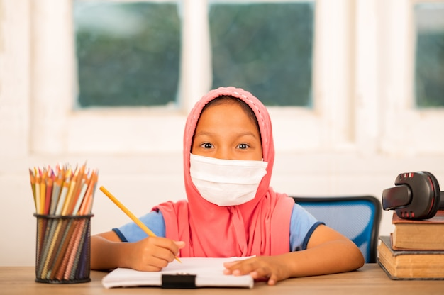 Muslim girls wearing sanitary masks studying online at home to reduce social distance and prevent communicable diseases Premium Photo