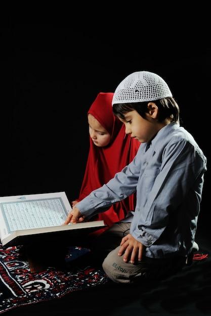 Muslim kids reading holy koran on black background Premium Photo