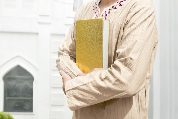 Muslim man holding quran Premium Photo