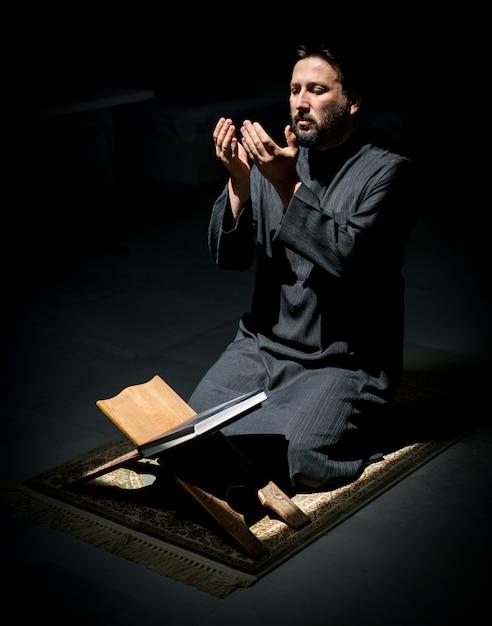 Muslim man praying for god in dark room at ramadan Premium Photo