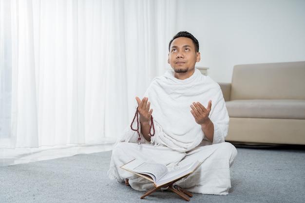 白の伝統的な服で祈るイスラム教徒の男性 Premium写真