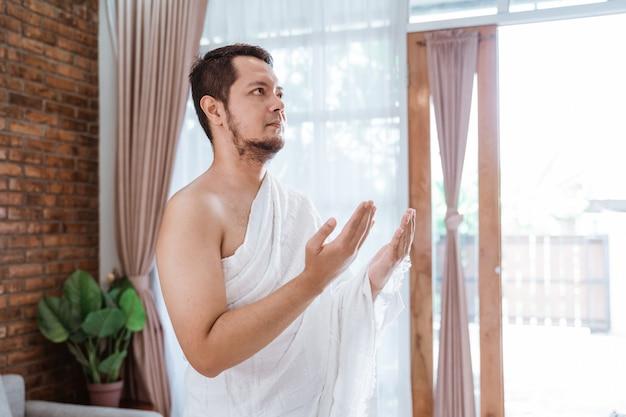 Muslim man praying wearing ihram clothes Premium Photo