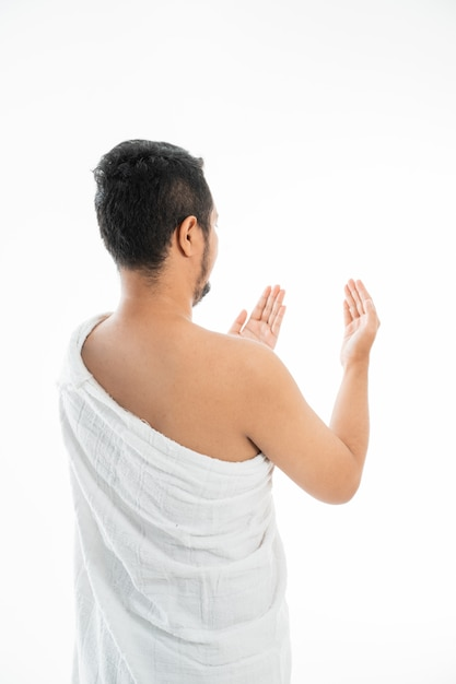 Muslim man praying in white traditional clothes Premium Photo