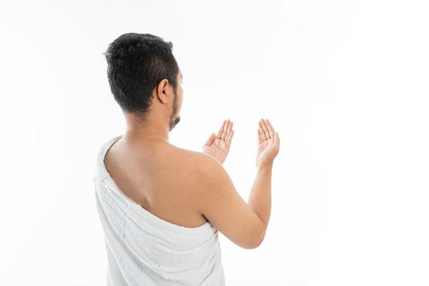 Muslim man praying in white traditional clothes Premium Photo