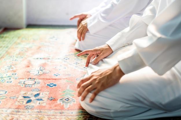 Muslim men praying in tashahhud posture Free Photo
