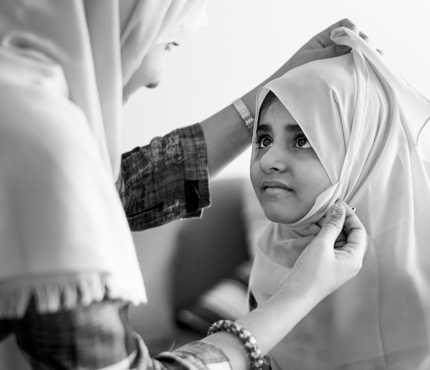 Muslim mom teaching daughter how to wear a hijab Free Photo