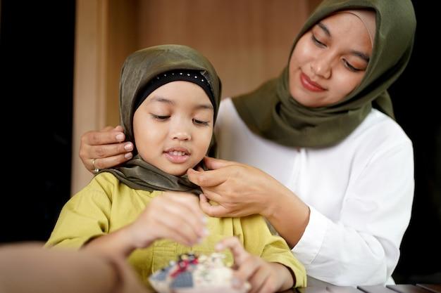 イスラム教徒の母親が娘にヒジャーブの着用方法を教えています。 Premium写真