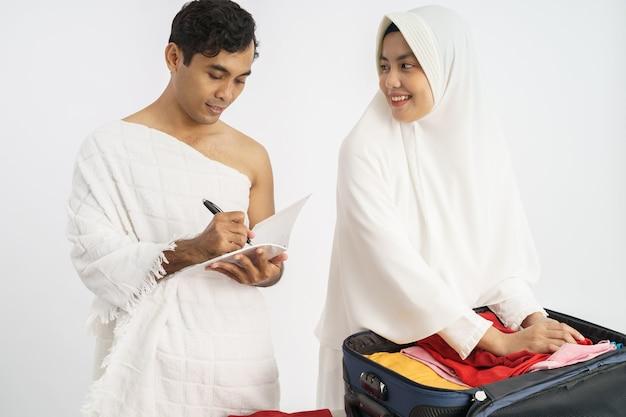 Жена и муж паломников-мусульман готовят предметы для хаджа в каабу Premium Фотографии