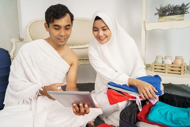 イスラム教徒の巡礼者の妻と夫がアイテムを準備します。 Premium写真