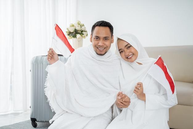 イスラム教徒の巡礼者の妻と夫とインドネシアの旗 Premium写真