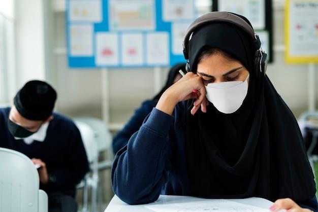 Studente musulmano che indossa una maschera studiando in una classe Foto Gratuite
