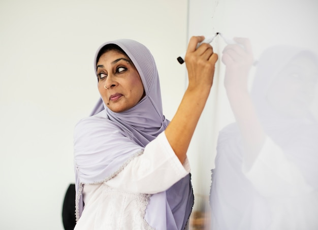 Muslim teacher writing on a white board Premium Photo