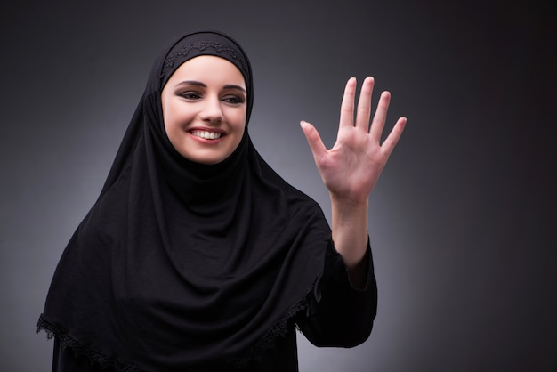 Muslim woman in black dress against dark background Premium Photo