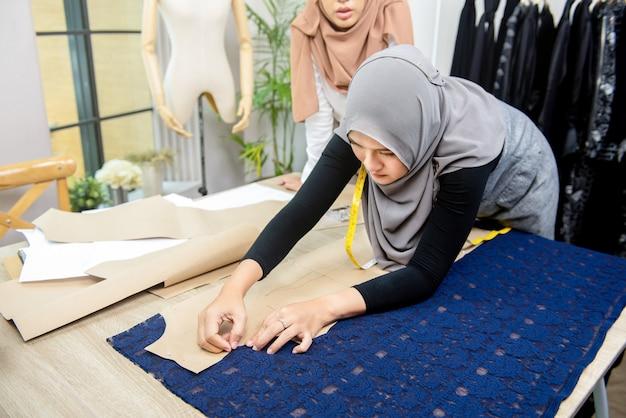 Muslim woman fashion designer pinning paper pattern on fabric Premium Photo