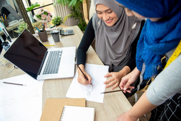 Muslim woman fashion designer team discussing dress sketch Photo