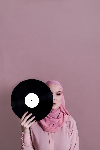 Muslim woman holding vinyl in front of face Free Photo