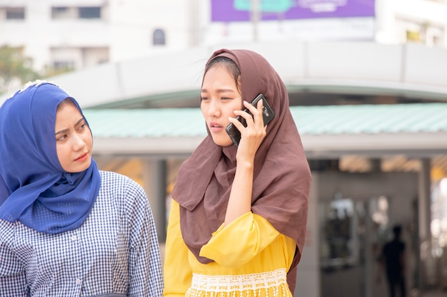 Muslim woman is on the phone while her friend is looking at her Premium Photo
