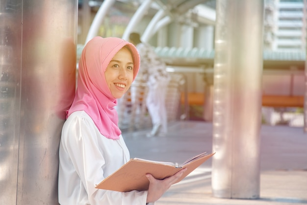 Muslim woman is reading book. she is smiling. Premium Photo