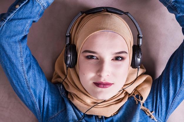 Muslim woman listening to music on headphones Free Photo