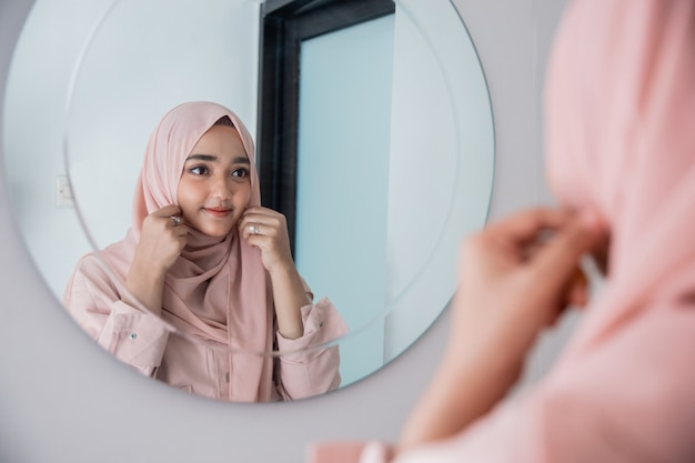 Muslim woman make up her self in the mirror Premium Photo