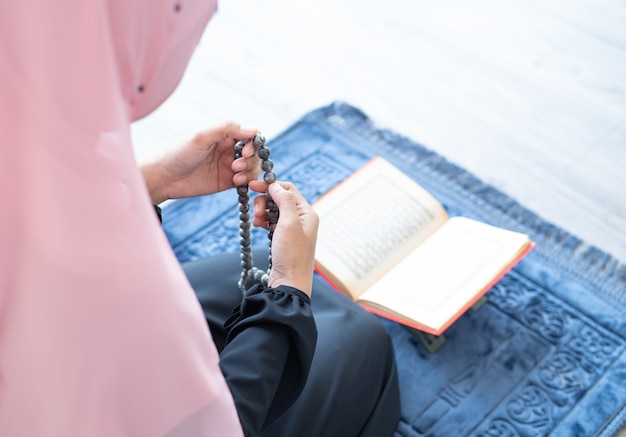 Muslim woman pray with beads and read quran Premium Photo