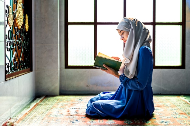 Muslim woman reading from the quran Premium Photo