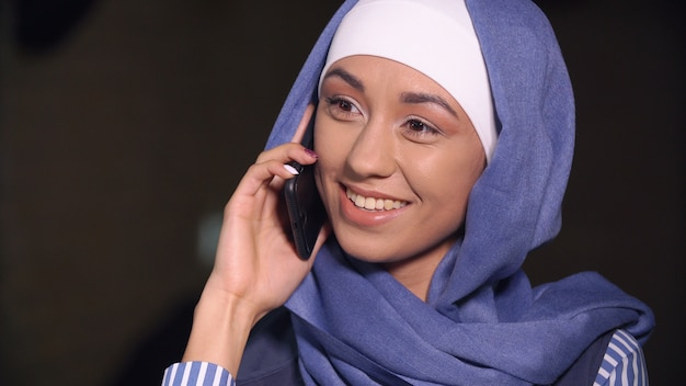Muslim woman smiling talking on a cell phone. Premium Photo