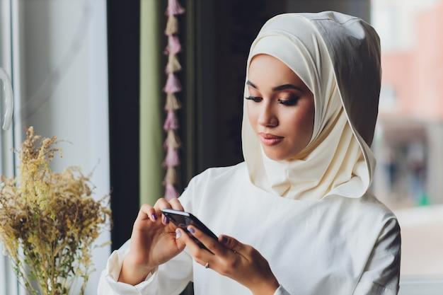 카페에서 휴대 전화 통화하는 이슬람 여성 프리미엄 사진