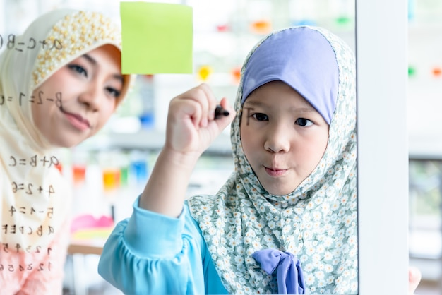 Muslim woman teaching child pupils by writing mathematical formulas on a glass board in Premium Photo