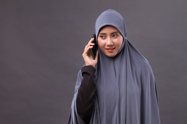 Muslim woman using smartphone call, wireless internet device Premium Photo