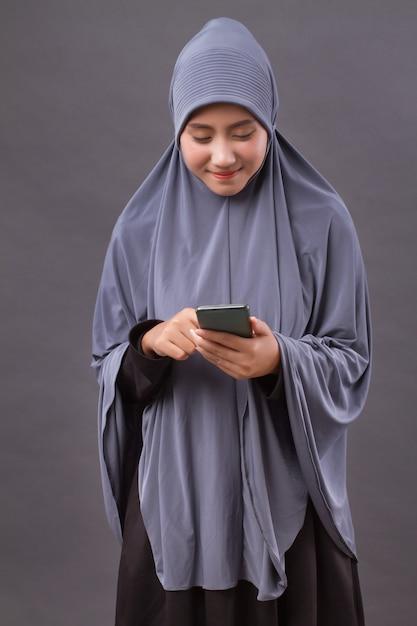 Muslim woman using smartphone, wireless internet device Premium Photo