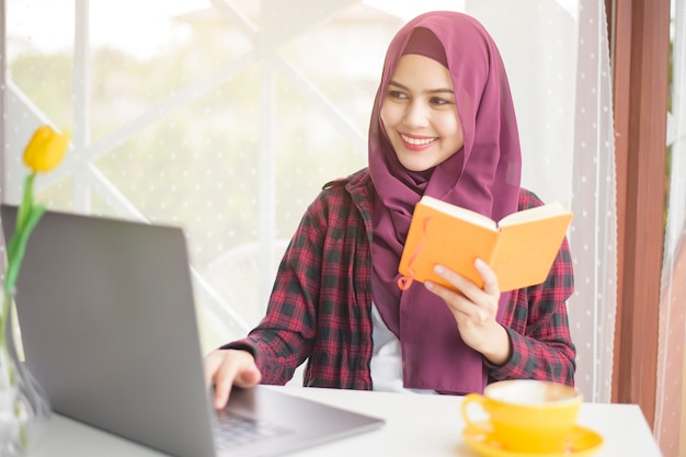 Muslim woman with hijab is working with laptop computer in coffee shop Premium Photo