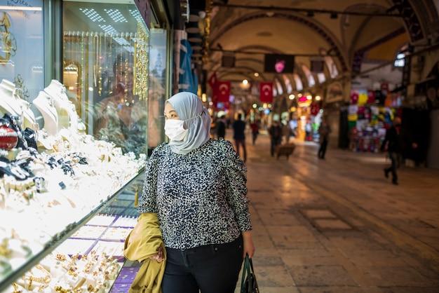 Donna musulmana con una maschera nel bazar in turchia durante la pandemia di covid-19 Foto Gratuite