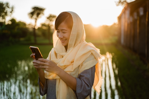 スマートフォンを屋外でイスラム教徒の女性 Premium写真