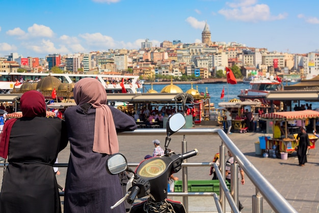 Muslim women looking istanbul panorama with galata tower during summer sunny day. istanbul, turkey. Premium Photo